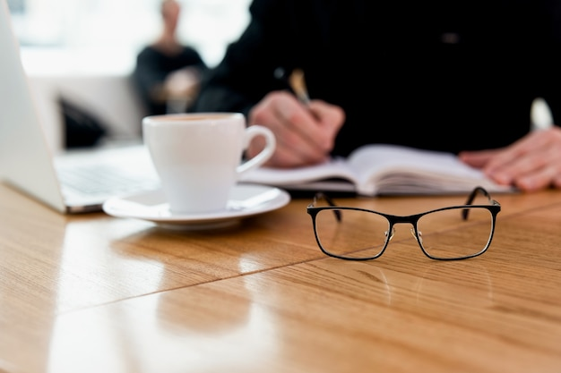 De mens heeft geen bril meer nodig! jonge geconcentreerde freelancer in zwart shirt die een ontmoetingsdatum in zijn dagboek schrijft en geniet van geweldige cappuccino in de coffeeshop. moderne laprop en witte mok op tafel.