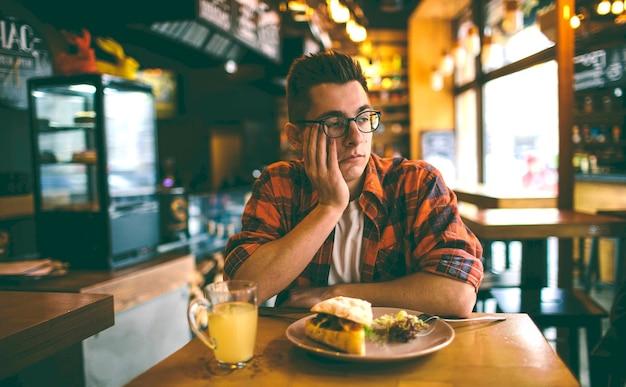 De mens heeft geen eetlust in het restaurant