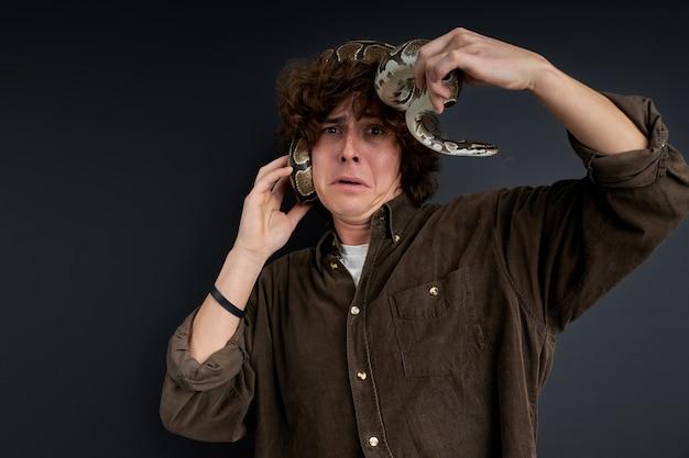 De mens heeft paniek, hij probeert een levende slang uit zichzelf te verwijderen, staat met verlies geïsoleerd op zwarte achtergrond