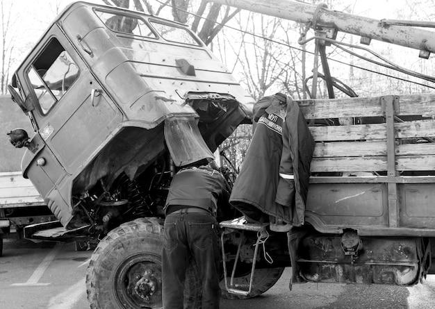 De mens herstelt een vrachtwagen door een cabine op te heffen