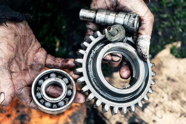 De mens herstelt motor van tractor, landbouwmachines. lagers in vuile handen.