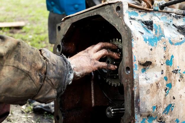 De mens herstelt motor van tractor, landbouwmachines. peiling, tandwielen, close-up.