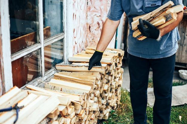 De mens houdt brandhout, steekt hij het snijden van hout in stapel hout houtstapel