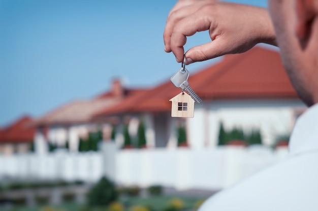 De mens houdt de sleutels van het huis in zijn handen