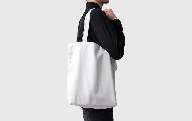 De mens houdt de stof van het zakcanvas voor model lege die malplaatje op grijze achtergrond wordt geïsoleerd.