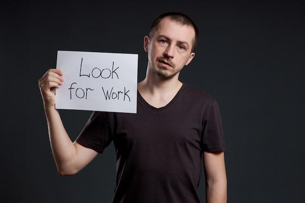 De mens houdt een bord met de woorden op zoek naar werk, werkloosheid en crisis