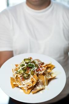 De mens houdt een bord met nacho's met tortillachips