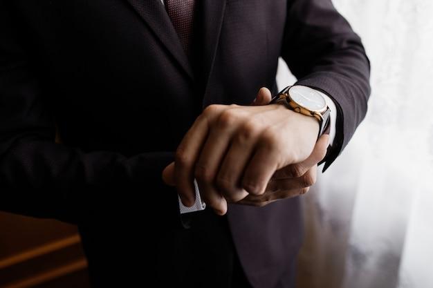 De mens houdt een horloge om zijn pols