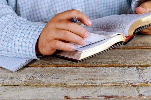 De mens houdt een pen in zijn hand met een open heilige bijbel die voor hem ligt