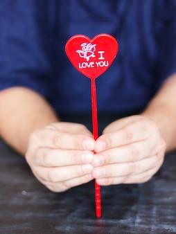 De mens houdt een rood hart met de woorden i love you in his hands