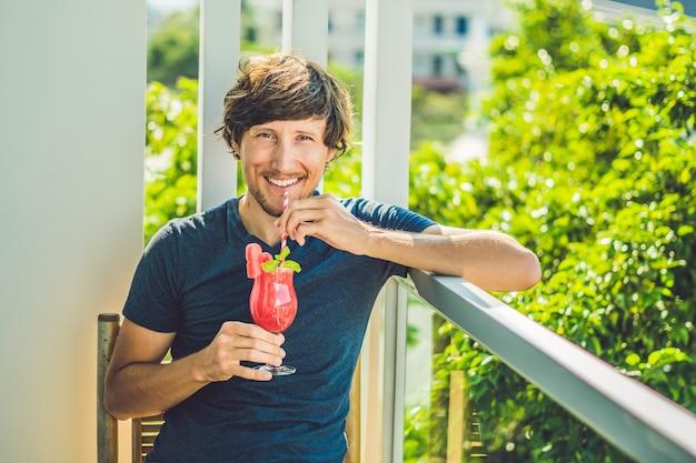 De mens houdt gezonde watermeloen smoothie met munt en gestreepte rietjes op een hout.