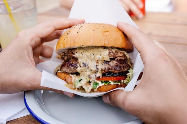 De mens houdt hamburger met handen dicht omhoog