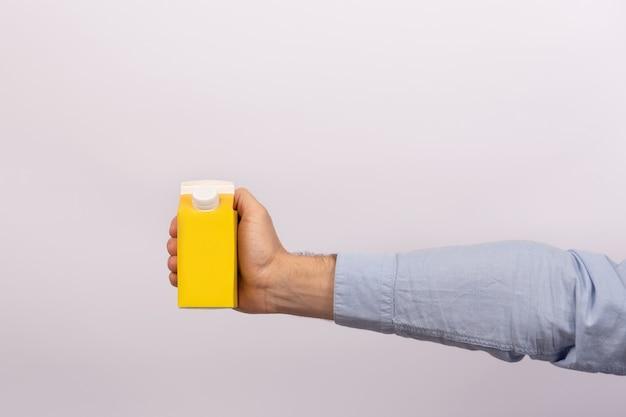 De mens houdt karton van sap of melk op witte achtergrond. bespotten.