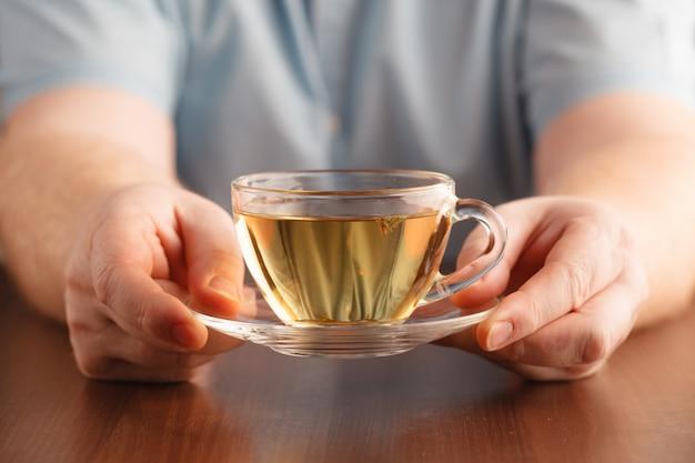 De mens houdt kop in hand en biedt thee aan