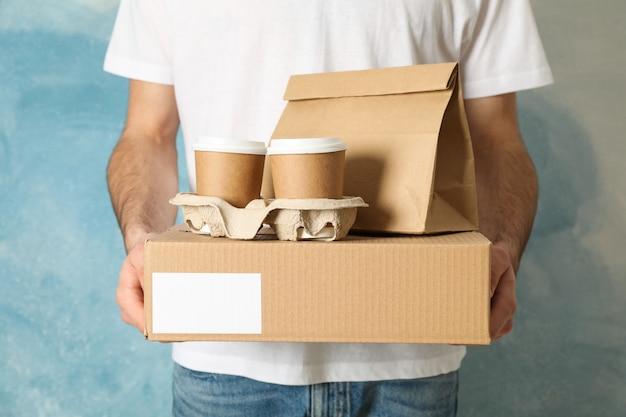 De mens houdt lege doos, koffiekopjes en document pakket binnen, ruimte voor tekst