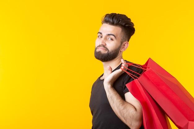 De mens houdt rode boodschappentassen op een gele muur. het concept van winkelen in de supermarkt