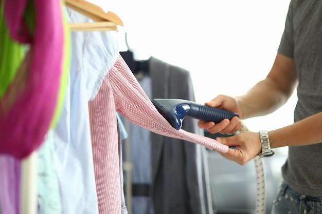 De mens houdt stoomboot in zijn handen en overhemd op hanger strijken