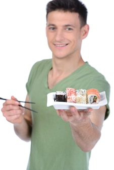 De mens houdt sushi in de hand en glimlacht.