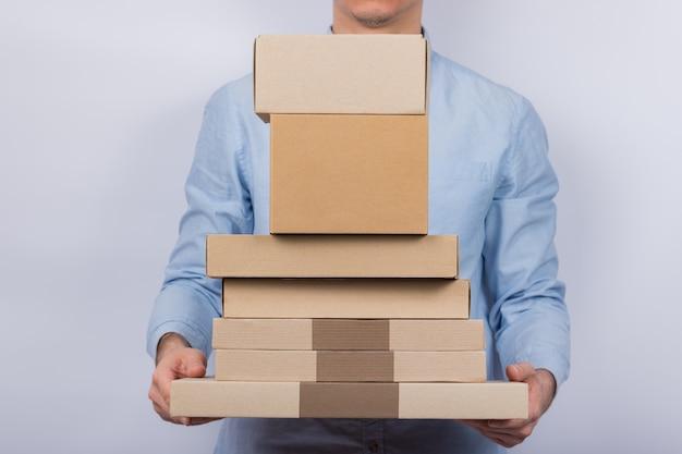 De mens houdt veel kartonnen dozen.