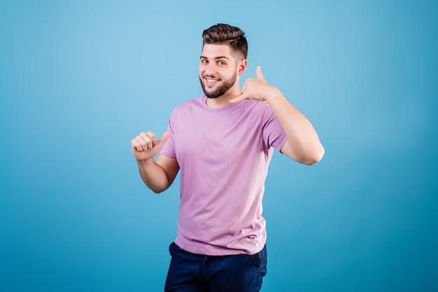De mens imiteert telefoongesprek met hand spreken geïsoleerd over blauw