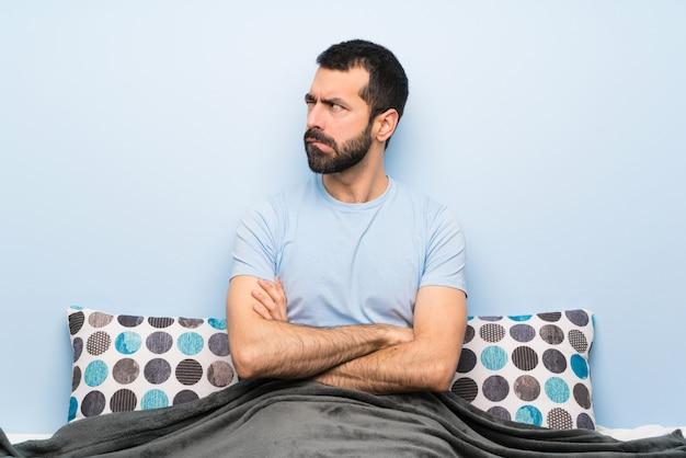 De mens in bed met verwart gezichtsuitdrukking