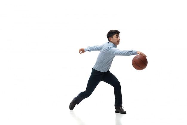 De mens in bureau kleedt het spelen van basketbal op witte ruimte. ongewone look voor zakenman in beweging, actie. sport, gezonde levensstijl.