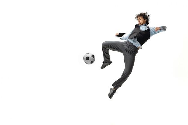 De mens in bureaukleren die voetbal of voetbal met bal op witte ruimte spelen. ongewone look voor zakenman in beweging, actie. sport, gezonde levensstijl.