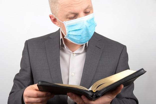 De mens in een pak met een medisch masker op zijn gezicht bestudeert de bijbel.