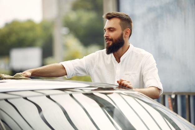 De mens in een wit overhemd veegt een auto in een autowasserette af