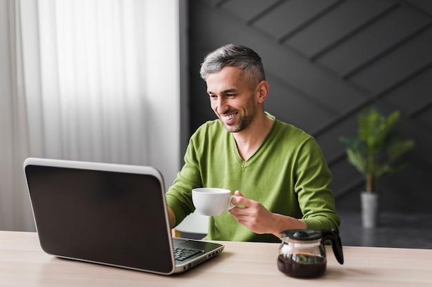 De mens in groen overhemd glimlacht en het gebruiken van zijn laptop