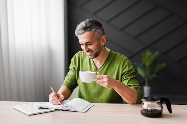 De mens in groen overhemd houdt kop en schrijft