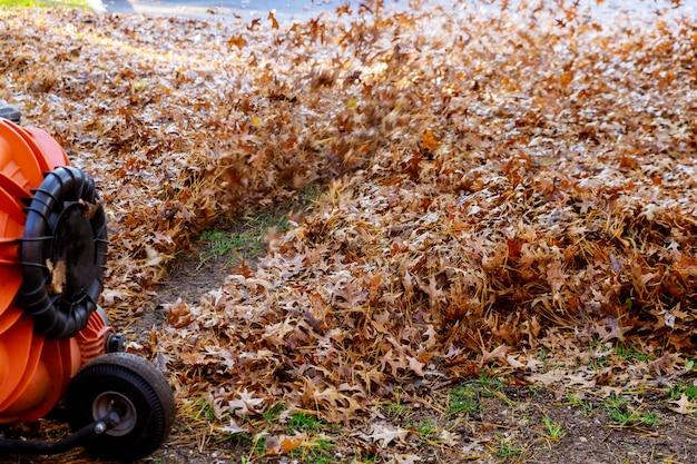 De mens in het werk blaast gele en rode gevallen de herfstbladeren in schoonmakende werf met windturbine weg