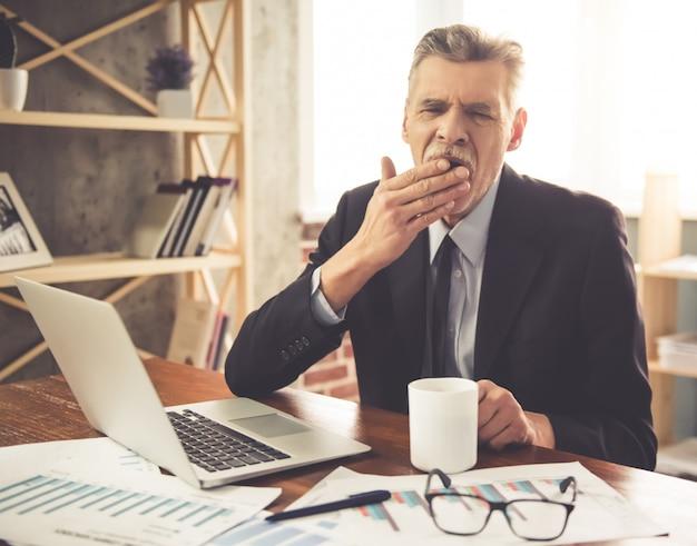 De mens in klassiek kostuum geeuwt terwijl het werken in bureau