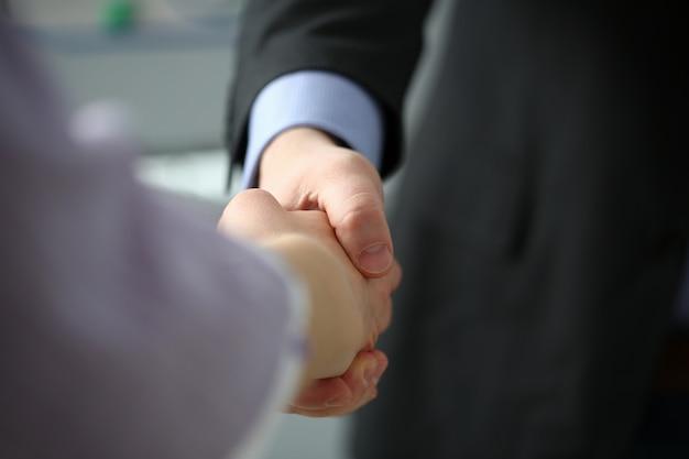 De mens in kostuum en band geeft hand als hallo in bureauclose-up. vriend welkom bemiddeling aanbod positieve introductie dank gebaar top deelnemen uitvoerende goedkeuring motivatie mannelijk arm staking koopje