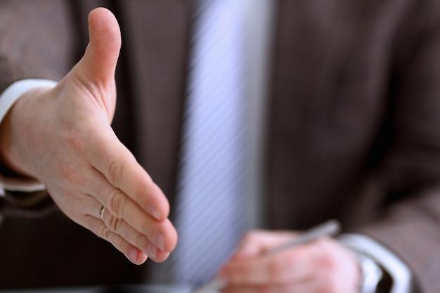 De mens in kostuum en band geeft hand als hallo in bureauclose-up. vriendelijke ontvangst, bemiddelingsaanbieding, positieve introductie, bedankt gebaar, topdeelname goedkeuring, motivatie, mannelijke arm, koopje
