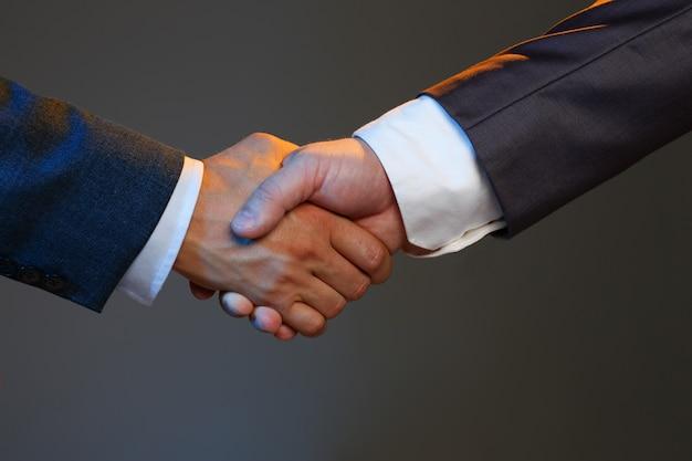 De mens in kostuum schudt hand zoals hallo in bureau