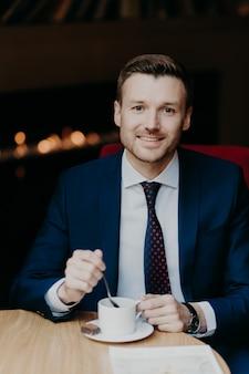 De mens in luxepak, drinkt koffie, zit bij houten lijst in cafetaria, heeft prettige glimlach en aantrekkelijke blik