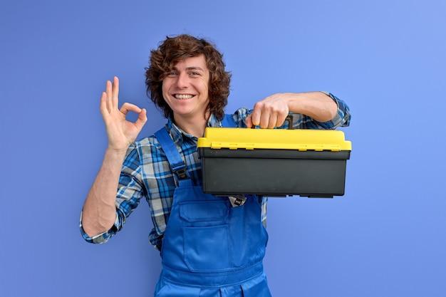 De mens in overall houdt de doos van de gereedschapskist die op blauwe studioachtergrond wordt geïsoleerd, die ok gebaar toont