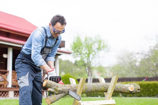 De mens in overall zaagt hout met kettingzaag gebruikend zaagbok