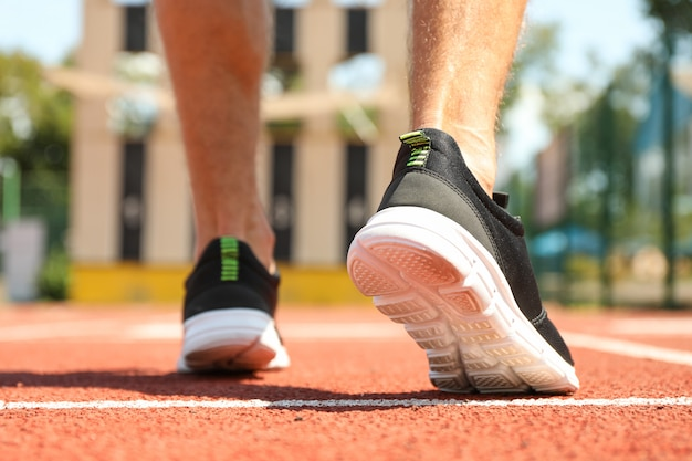 De mens in tennisschoenen op rode atletische renbaan, sluit omhoog