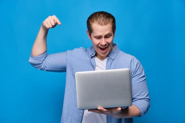 De mens in vrijetijdskleding op blauw staat druk op knoop in laptop met glimlach te drukken.