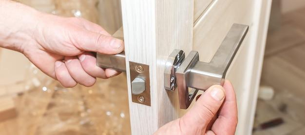 De mens installeert de deurklink. reparatie werkt. onderhoud in het appartement.