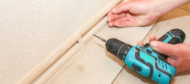 De mens installeert de plint met een boor. reparatie werkt binnen. renovatie in de flat.