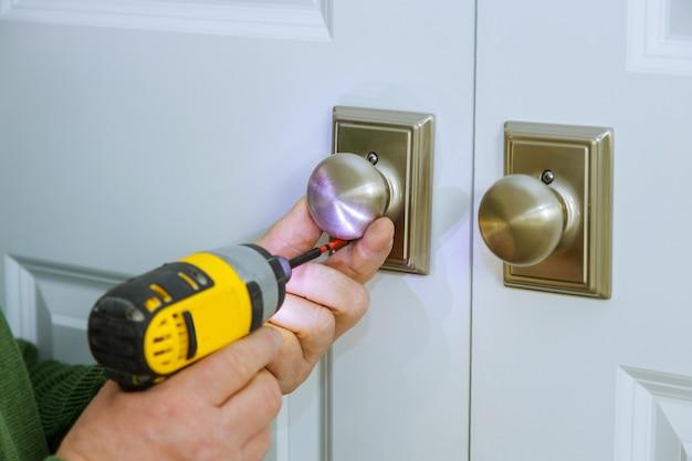 De mens installeert het handvat van de deuren