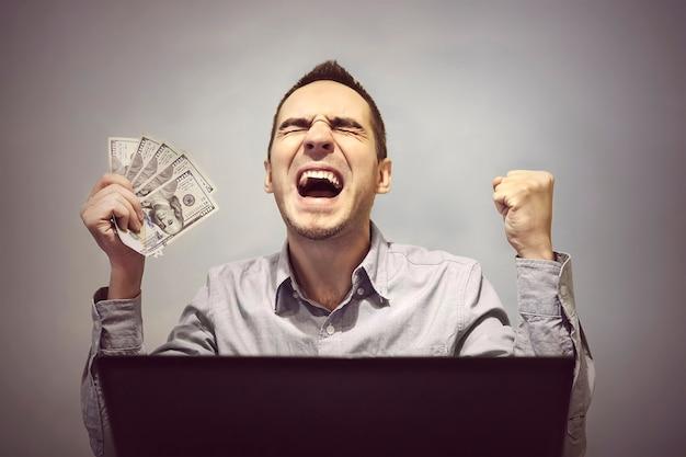 De mens is blij achter de computer om 500 dollar vast te houden. winnen in een online casino. profiteer van online handelen in aandelen. makkelijk geld. verdiensten op internet.