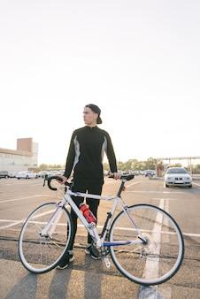 De mens is een fietser met donkere sportkleding en een pet met een fiets op de achtergrond van het stadslandschap