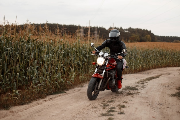 De mens is een motorrijder in zwarte outfit met een helm die in het veld met maïs rijdt. conceptreizen