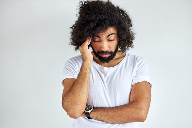 De mens is moe om ontevredenheid van anderen op het werk te horen. ontevreden mannelijke tribune die het hoofd aanraakt