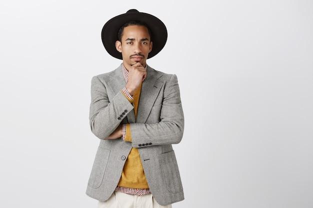 De mens is niet zeker van je. portret van een twijfelachtige knappe man in trendy jasje en hoed, hand op kin, fronsend, achterdochtig kijkend tijdens het denken, twijfels of ongeloof over grijze muur