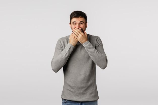 De mens kan lach niet houden bij ernstige vergadering, die glimlach achter mond verbergen. vrolijke schattige volwassen man in grijze trui, druk handen op lippen en grinnik, probeer geen lawaai te maken, roddelende collega's op kantoor